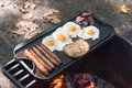 Cooking food over an open fire eggs bacon sausage and toast on a cast iron grill wood flame Stock Photos