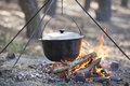 Cooking in the forest camping kettle over burning campfire Stock Photography