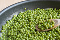 Cooking green peas in black frying pan with wooden spoon Royalty Free Stock Photo