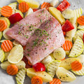 Cooking healthy food - raw ingredients: potatoes, zucchini, carrots, onions, garlic, peppers and fish sea bass Royalty Free Stock Photo