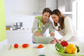 Cooking with help of internet couple in home kitchen looking for lunch recipe Royalty Free Stock Photography