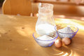 Cooking jug with milk two bowls with sugar and flour and two fresh eggs on a table outside cakes Stock Image