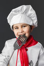 Cooking little boy preparing healthy food on kitchen over grey cuisine background cook Stock Photo