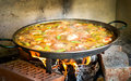 Cooking and making a traditional spanish paella over open fire w with wood coal made from chicken rabbit meat in Stock Photos