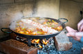 Cooking and making a traditional spanish paella over open fire w with wood coal made from chicken rabbit meat in Royalty Free Stock Photos