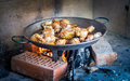 Cooking and making a traditional spanish paella over open fire with wood coal made from chicken rabbit meat in Stock Photos
