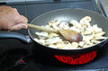 Cooking mushrooms in a pan on a stove. Royalty Free Stock Photo