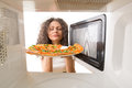 Cooking pizza in the microwave girl gets a out of Royalty Free Stock Photography