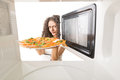 Cooking pizza in the microwave girl gets a out of Royalty Free Stock Images