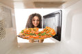 Cooking pizza in the microwave girl gets a out of Royalty Free Stock Photo