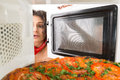 Cooking pizza in the microwave girl gets a out of Stock Photo