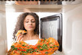 Cooking pizza in the microwave girl gets a out of Stock Photography