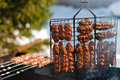 Cooking sausages on grill Stock Images