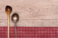 Cooking and silver spoon on a checkered table cloth wooden board Stock Photography