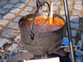 Cooking soup over burning campfire Royalty Free Stock Photo