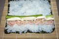 Cooking sushi rolls with nori seaweed sheets rice sumesi shrimp philadelphia cheese and cucumber on a bamboo mat makisu Stock Photos