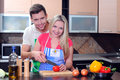Cooking young couple men and women in their kitchen at home preparing vegetables for salad Stock Photography