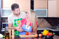 Cooking young couple men and women in their kitchen at home preparing vegetables for salad Royalty Free Stock Photography