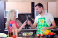 Cooking young couple men and women in their kitchen at home preparing vegetables for salad Royalty Free Stock Images