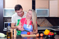 Cooking young couple men and women in their kitchen at home preparing vegetables for salad Royalty Free Stock Photo