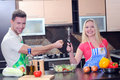 Cooking young couple men and women in their kitchen at home preparing vegetables for salad Stock Image