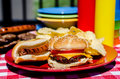 Cookout with cheeseburger hot dog and potato chips mustard and ketchup bottles bowls hamburger patties and hot dog wieners in Royalty Free Stock Photography