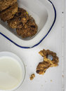 Cooky with milk and dish of cookies broken rustic home baked in an old enamel a glass on a rustic white table top Stock Photos