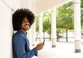 Cool black guy standing outside with mobile phone side portrait of a and earphones Stock Image