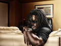 Cool black man with dreads on leather couch portrait of a and shot selective focus Royalty Free Stock Photo