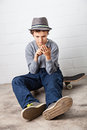 Cool boy sitting on his skateboard holding a smartphone teenage in hands with which he is playing around with Stock Photo