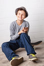 Cool boy sitting on his skateboard laughing a teenage holding a smartphone in hands with which he is playing around with he is Royalty Free Stock Images