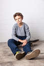 Cool boy sitting on his skateboard a teenage looking straight into the camera Royalty Free Stock Photo