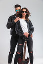 Cool couple in leather jackets standing embraced holding electri Royalty Free Stock Photo