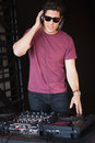 Cool dj in sunglasses spinning the decks at nightclub Royalty Free Stock Photography