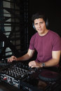 Cool dj working on a sound mixing desk at the nightclub Royalty Free Stock Image