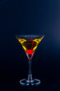 Cool drink yellow cocktail and red cherry in the dark Stock Photo