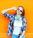 Cool girl having fun listens music in headphones over colorful Royalty Free Stock Photo