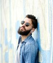 Cool guy with beard listening to music with earphones close up portrait of a Stock Images
