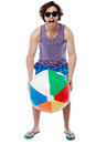 Cool guy playing with beach ball young handsome holding a Stock Photography