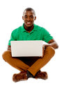 Cool guy seated on floor using laptop Stock Photography