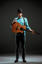 Cool guy standing with guitar on dark background Royalty Free Stock Photo