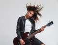 Cool headbanging rock and roll woman playing electric guitar Royalty Free Stock Photo