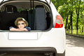 Cool little boy ready for his vacation sitting with head resting on arms in the open back of a hatchback car with Royalty Free Stock Photography