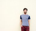 Cool male fashion model with beard leaning against wall Royalty Free Stock Photo