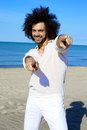 Cool male model on beach smiling and pointing fingers posing italian active man having fun in front of the ocean Stock Photography