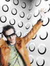 Cool man wearing headphones and sunglasses young in front of spotty wall Royalty Free Stock Photos