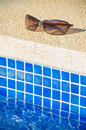 Cool poolside shades with sleek holiday villas reflected in the lenses Royalty Free Stock Photos