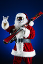 Cool santa claus is standing in the ski mask and holding a skiing christmas Royalty Free Stock Photography