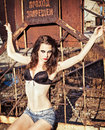 Cool sexy girl clings to a rusty metallic lattice Royalty Free Stock Photo