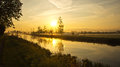 Cool sunrise above dutch paddock a with view over a canal and distant farms on a morning Stock Photography